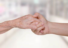 Young nurse holding old patient hand. In hospital Royalty Free Stock Photos