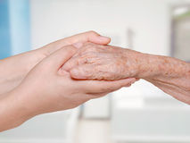 Young nurse holding old patient hand. In hospital Stock Image