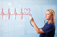 Young nurse listening to abstract pulse with red heart Stock Images