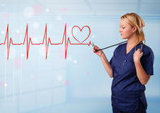 Young nurse listening to abstract pulse with red heart Stock Photos