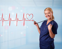 Young nurse listening to abstract pulse with red heart Royalty Free Stock Photography