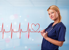 Young nurse listening to abstract pulse with red heart Stock Photo