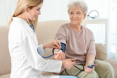 Young nurse measuring blood pressure of elderly woman. Young nurse measuring blood pressure of elderly women at home Stock Photography