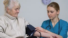 Young nurse measuring disabled elderly female blood pressure and taking records