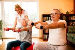 Nurse at nursing home helps senior people to doing exercises. Young nurse at nursing home helps senior people to doing exercises stock photo