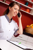 Young nurse phoned and smiles Stock Images