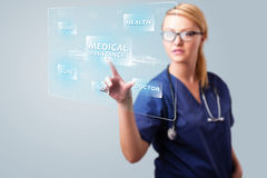 Young nurse pressing modern medical type of buttons Stock Images