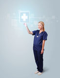 Young nurse pressing modern medical type of buttons Royalty Free Stock Image