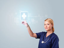 Young nurse pressing modern medical type of buttons Stock Photography