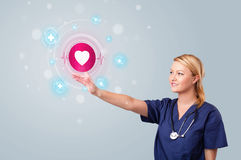 Young nurse pressing modern medical type of buttons Royalty Free Stock Images