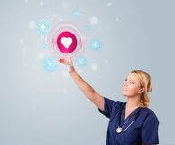 Young nurse pressing modern medical type of buttons Royalty Free Stock Photos