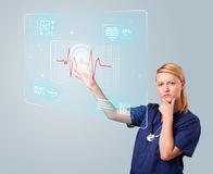 Young nurse pressing modern medical type of buttons Stock Photos