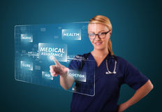 Young nurse pressing modern medical type of buttons Royalty Free Stock Photography