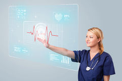 Young nurse pressing modern medical type of buttons Royalty Free Stock Photo