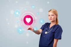 Young nurse pressing modern medical type of buttons Stock Photo