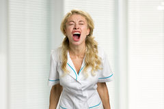 Young nurse screaming in despair. Very stressed beautiful young female doctor screaming loudly in frustration with closed eyes Stock Image