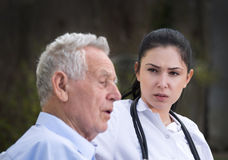 Young nurse with senior man in courtyard. Pretty young caregiver sitting with senior men on the bench in the courtyard Royalty Free Stock Image