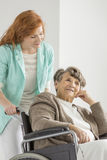 Young nurse taking care on senior. Women on wheelchair at retirement home Royalty Free Stock Images