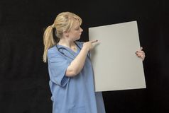 Young nurse in twenties pointing to a blank placard board. Taken on a black background Stock Photos