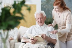 Nurse with cup of tea. Young nurse in uniform standing with a cup of tea next to disabled elder reading a book royalty free stock photos