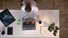 Young nurse in white coat typing on laptop, phone with chromakey lying on table, topshot, medical concept.  stock video