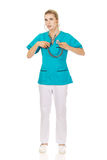 Young nursre or female doctor listen her own heart.  royalty free stock photography