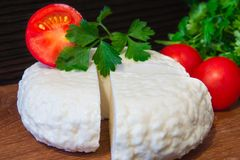 Young oak cheese cutting Board with tomatoes and parsley. Mozarella for pizzas and salads. Stock Photos