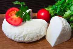 Young oak cheese cutting Board with tomatoes and parsley. Mozarella for pizzas and salads. Stock Images