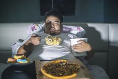 Young obese man eats junk foods before sleep stock photo