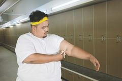 Young obese man measuring fat layer of his arm stock images