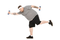 Young obese man running with dumbbells and looking at camera. Isolated on white Royalty Free Stock Photography