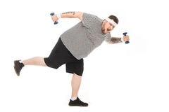 Young obese man running with dumbbells and looking at camera Royalty Free Stock Photography