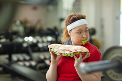 Young Obese Woman Hiding Secret Obsession with Food. Portrait of young overweight woman eating big greasy fattening sandwich at work out in gym, concept of food stock images