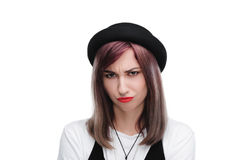 Young offended girl in black hat looking at camera Stock Image