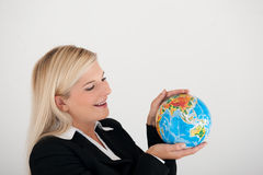 Young office busines woman holding a globe. Young office busines woman in a suit holding a globe stock photos