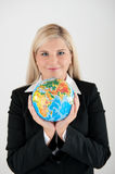 Young office busines woman holding a globe. Young office busines woman in a suit holding a globe stock photo