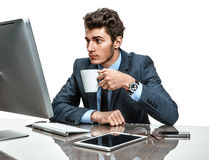 Young office clerk having a coffee time in office sitting at the table. Photos of modern businessman at the workplace Royalty Free Stock Images