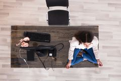 Female Worker Meditating On Top Of The Desk royalty free stock image