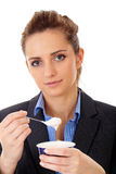 Young office girl eat yoghurt for her break Stock Images
