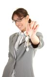 Young office girl with key. Young girl in a gray business suit on white background Royalty Free Stock Image