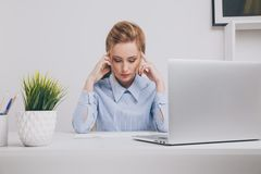 Young office girl sitting at her workplace feeling bad. Woman has a headache. stock photo