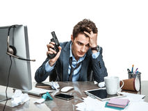 Young office man with gun wants to commit suicide. Modern office man at working place, depression and crisis concept Royalty Free Stock Image