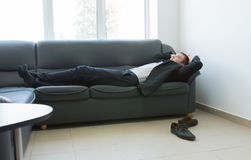 Young Office Man Lying on Couch During Break Stock Images