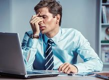 Young office man with pain in his head or an eye. Photo of man suffering from stress or a headache grimacing in pain. Business concept stock photos