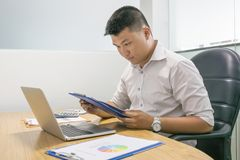 Office man reading financial document in the company royalty free stock photography