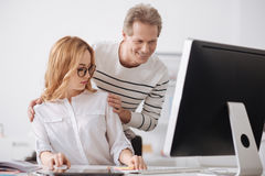 Young office manager collaborating with senior colleague at work royalty free stock image