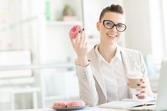 Having break in office. Young office manager with donut and coffee looking at camera by her desk during break for some snack Royalty Free Stock Photography