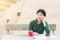 Young office woman talking to someone on her mobile phone with H. Appy Facial Expression. A wooden table outside the building have sun warm light Stock Photos