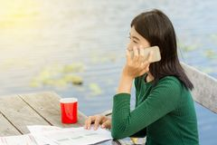 Young office woman talking to someone on her mobile phone with H. Appy Facial Expression. A wooden table outside the building have sun warm light Royalty Free Stock Photo