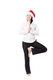 Young office woman in yoga pose in santa claus hat on white back. Smiling young office female in formalwear wearing white shirt and red Santa Claus Christmas hat Royalty Free Stock Images